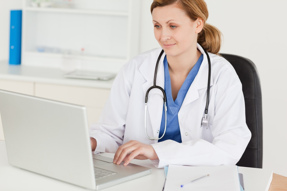 Attractive female doctor working on her laptop in her office